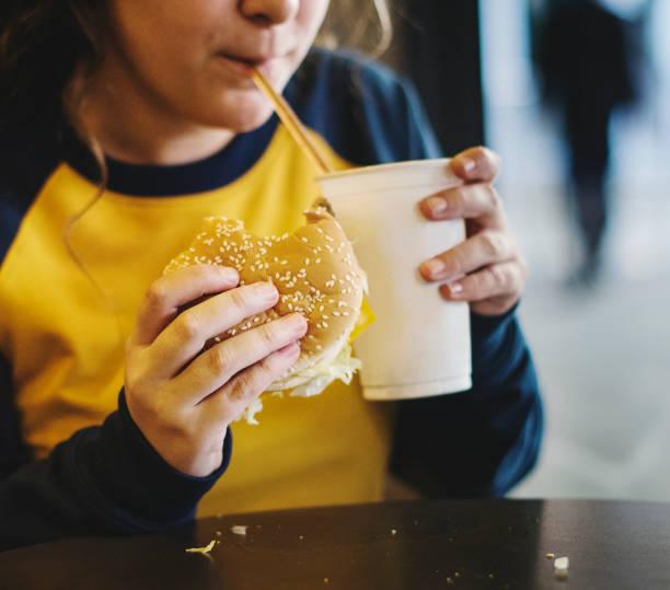close up of teenage girl eating hamburger obesity concept - niezdrowe jedzenie zdjęcia i obrazy z banku zdjęć