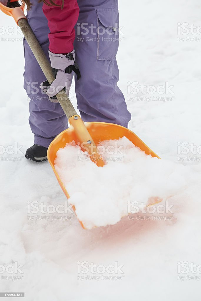 Close Up Of Teenage Girl Shovelling Snow From Path stock photo