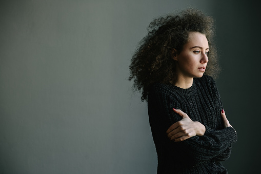 Close Up Of Teenager With Depression And Bulimia Standing Alone In Grey Room Mental Problems With Depression And Bulimia Black And White Photo Stock Photo - Download Image Now