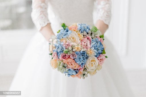 Close up of tender summer wedding bouquet with pale pink and peach roses, light blue hydrangea and white craspedia in the hands of the bride