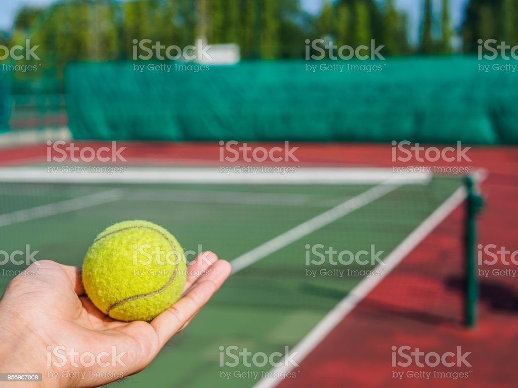 Close up of tennis ball on the hand at the tennis court. Sport active...