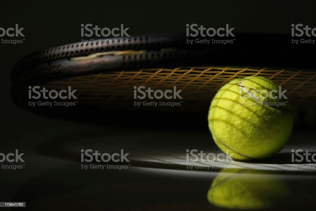Close up of tennis ball under tennis racket with shadow stock photo