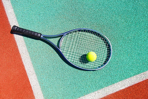 Close up of tennis racquet and ball on court stock photo