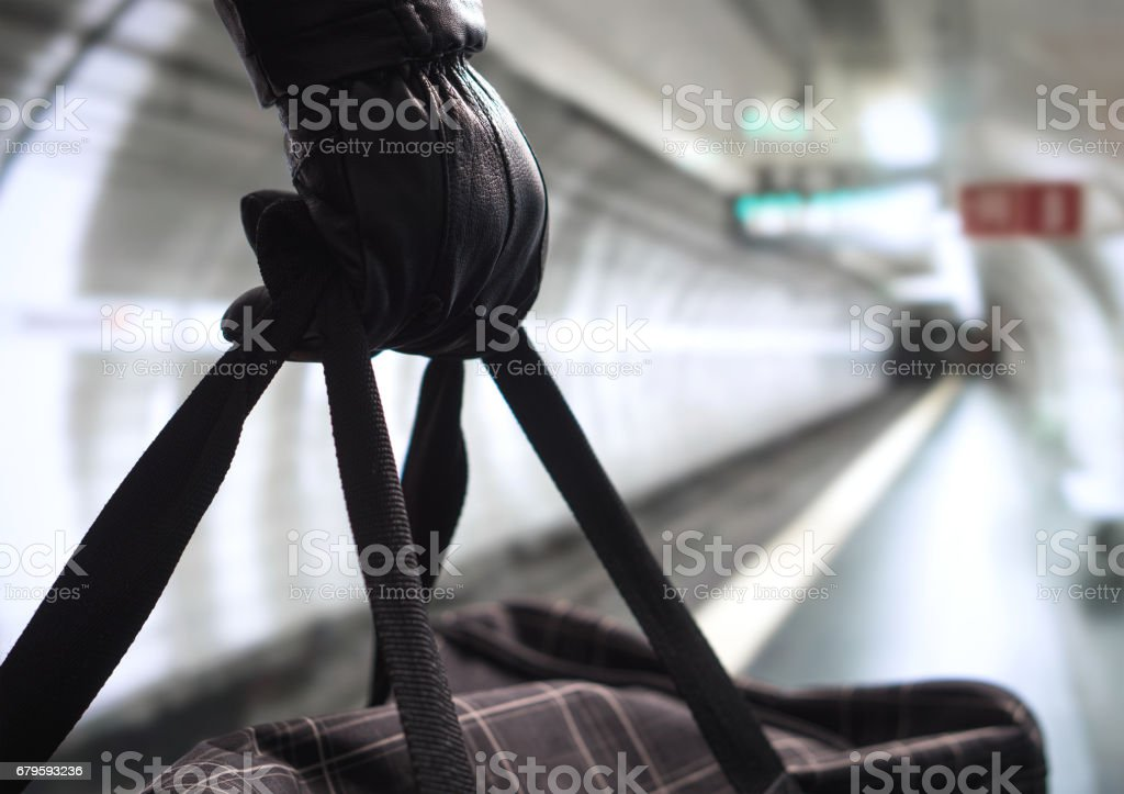 Close up of terrorist holding black bag in hand, possibly timebomb. Man planning a dangerous explosion in subway. Underground metro tunnel in the blurred background. Terrorism and security concept. stock photo