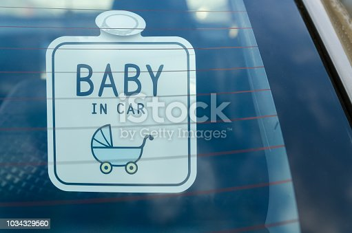 istock Close up of the baby in car board sign on the car back glass. 1034329560