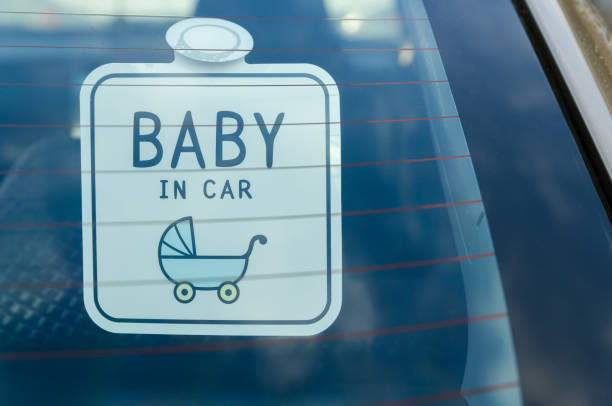 Close up of the baby in car board sign on the car back glass. stock photo