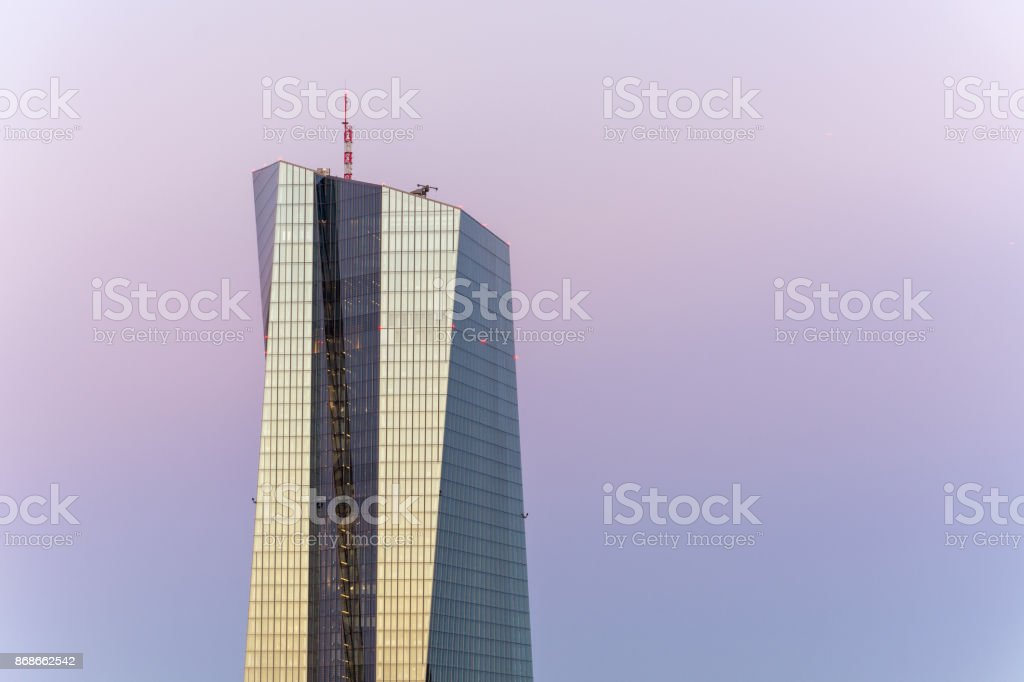 A close up of the EZB building in Frankfurt in the blue hour with a bridge in front and beautiful colors in the sky stock photo
