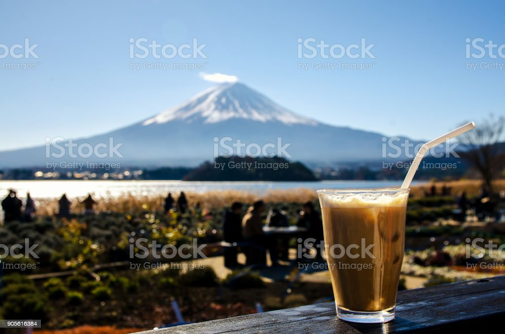 Close up of the ice coffee on a wooden floor with the Mount Fuji background. stock photo