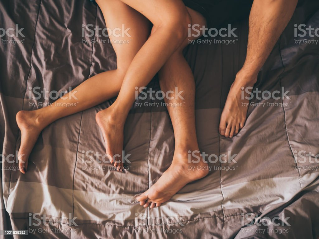 Close up of the legs of a couple on the bed. stock photo