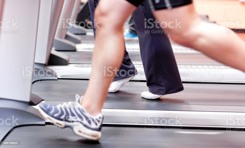 Close up of the legs of an athletic young woman exercising on a running machine stock photo