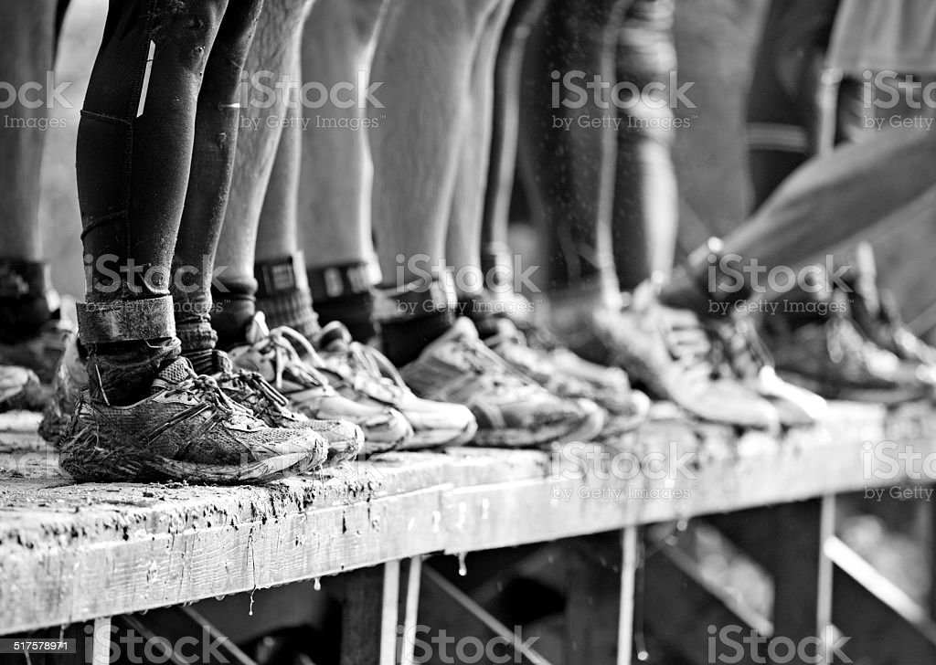 close up of the legs of mud runners stock photo
