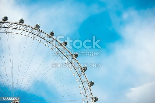 Close up of the London Eye from low angle view. It show a quarter of the ferris wheel, on the left side. The backgrounds is a blue sky with clouds.
