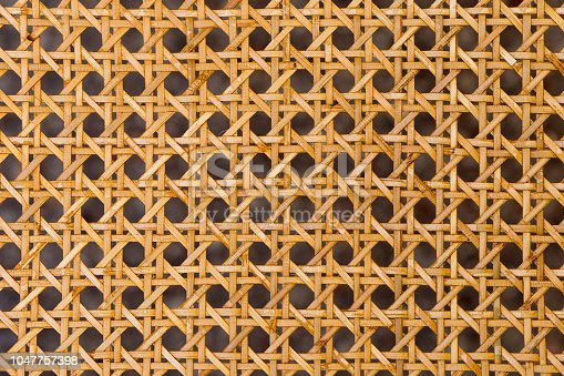 Close up of the pattern formed by open weave rattan cane on a chair seat