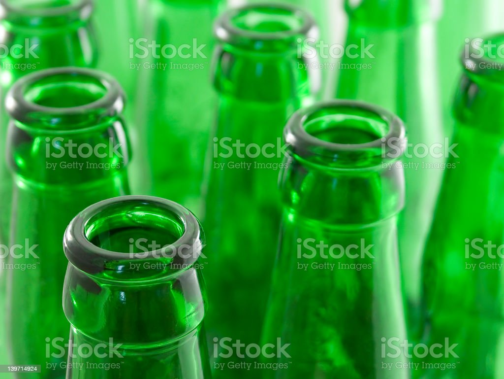 A close up of the top of rows of green beer bottles stock photo
