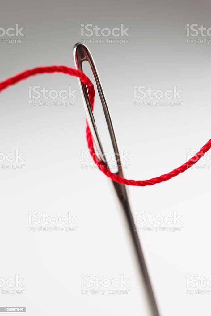 Close up of threading eye of a needle with red thread stock photo