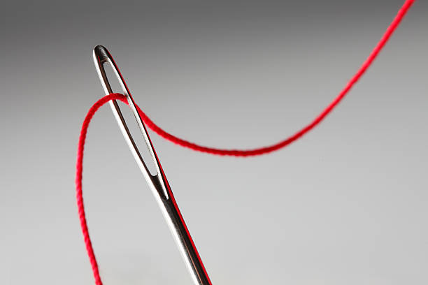 Close up of threading eye of a needle with red thread A close up of the eye of a needle being thread with red thread.  The thread gracefully curves across the image as it makes its way in and out of the eye of the needle.  It is photographed against a graduated light gray background.  Image is shot with a shallow depth of field. threading stock pictures, royalty-free photos & images