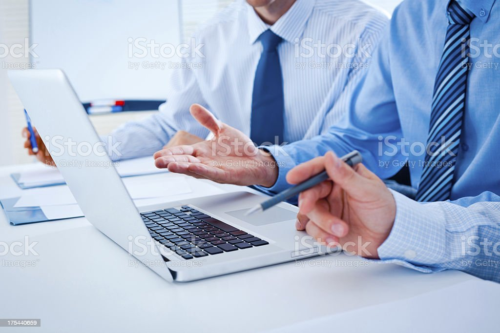 Close up of three businessmen at desk with laptop royalty-free stock photo