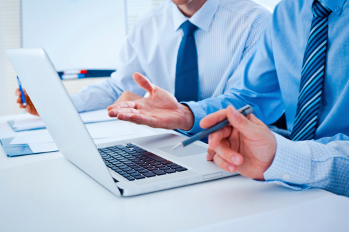 Close Up Of Three Businessmen At Desk With Laptop Stock Photo - Download Image Now