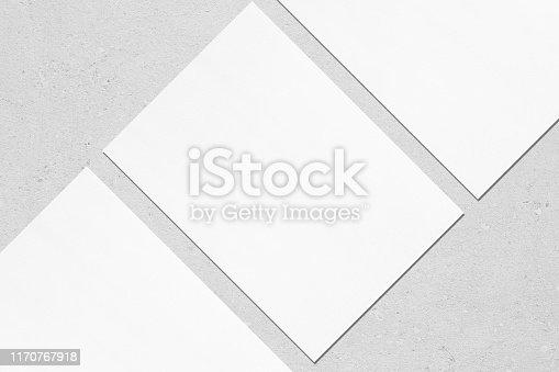 1171907064 istock photo Close up of three empty white rectangle poster mockups lying diagonally on grey concrete background 1170767918