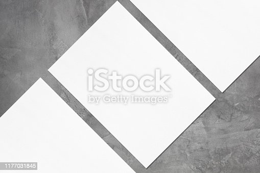 1173565159 istock photo Close up of three empty white rectangle poster mockups lying diagonally on grey concrete background 1177031845