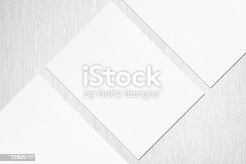 1173565159 istock photo Close up of three empty white rectangle poster or card mockups lying diagonally 1173565122