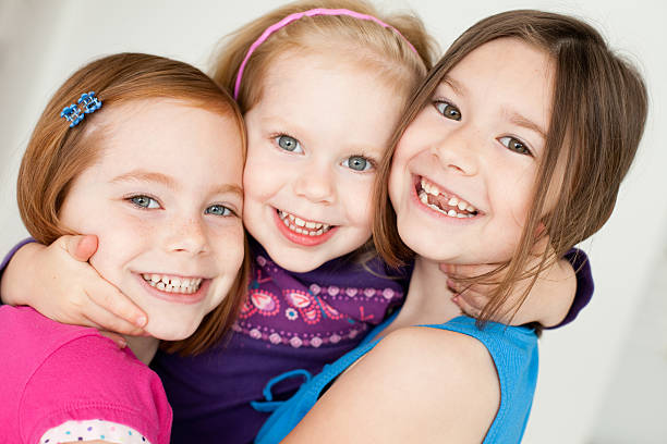 Close Up of Three Happy Sisters Hugging Each Other stock photo