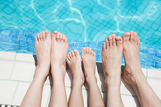 Close up of three people's legs by the pool side stock photo