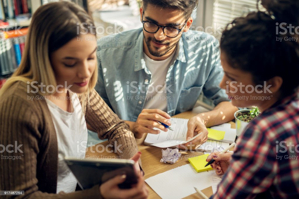 Close up of three young cheerful happy hardworking students sitting at the desk and looking in a tablet while doing homework in the library. stock photo