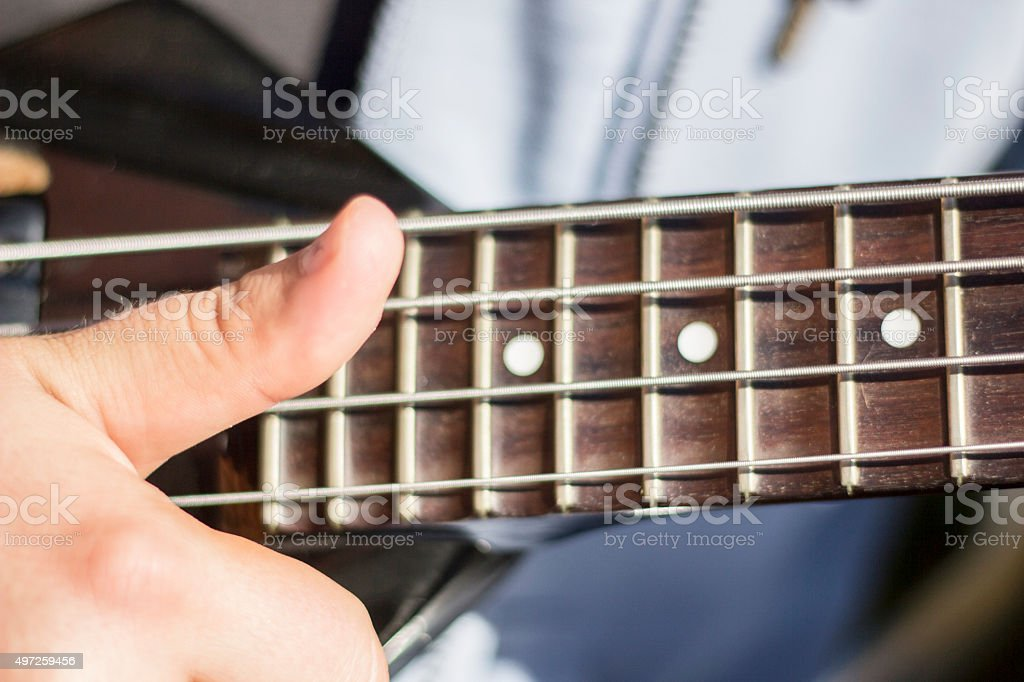 Close up of thumb on electric bass strings. Slapping bass guitar strings. stock photo