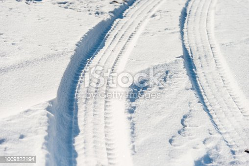 629589448 istock photo Close up of tire tracks in snow 1009822194