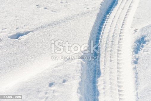 629589448 istock photo Close up of tire tracks in snow 1009822388