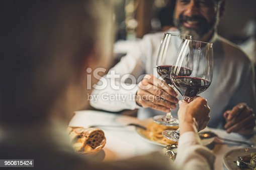 Close up of a couple toasting with red wine during lunch in a restaurant.