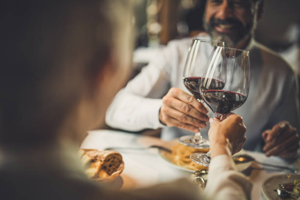 close up of toasting with wine in a restaurant! - couple lap stock photos and pictures