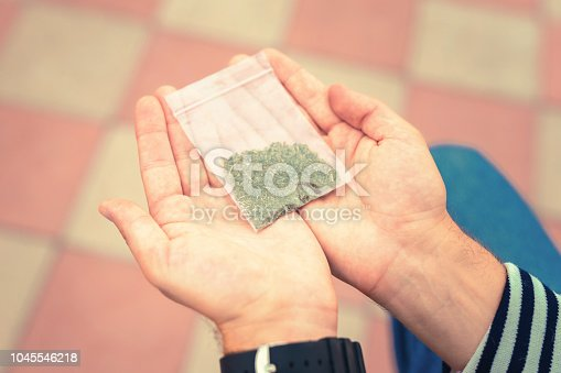 Last portion. Young man holding little package of tobacco in his two hands before smoking