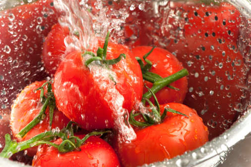 Close up of tomatoes being washed