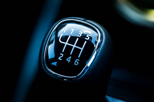 Close up of top of gear stick in car interior Close up color image depicting the top side of a gear stick (or stick shift) in a car interior. Focus is on the gear stick while the background is blurred pleasantly out of focus. Room for copy space. gearshift stock pictures, royalty-free photos & images