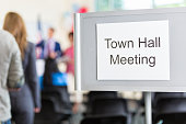 Group of people gather for town hall meeting. A 'Town Hall Meeting' sign is at the entrance of the meeting room. The crowd is blurred in the background.