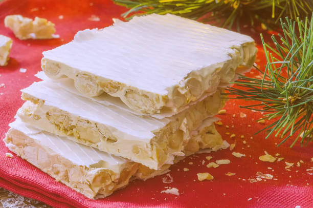 Close up of Turron, typical Christmas sweet in Spain. Almond nougat on red napkin  on dark wooden background with Christmas decoration, snow and fir tree. stock photo