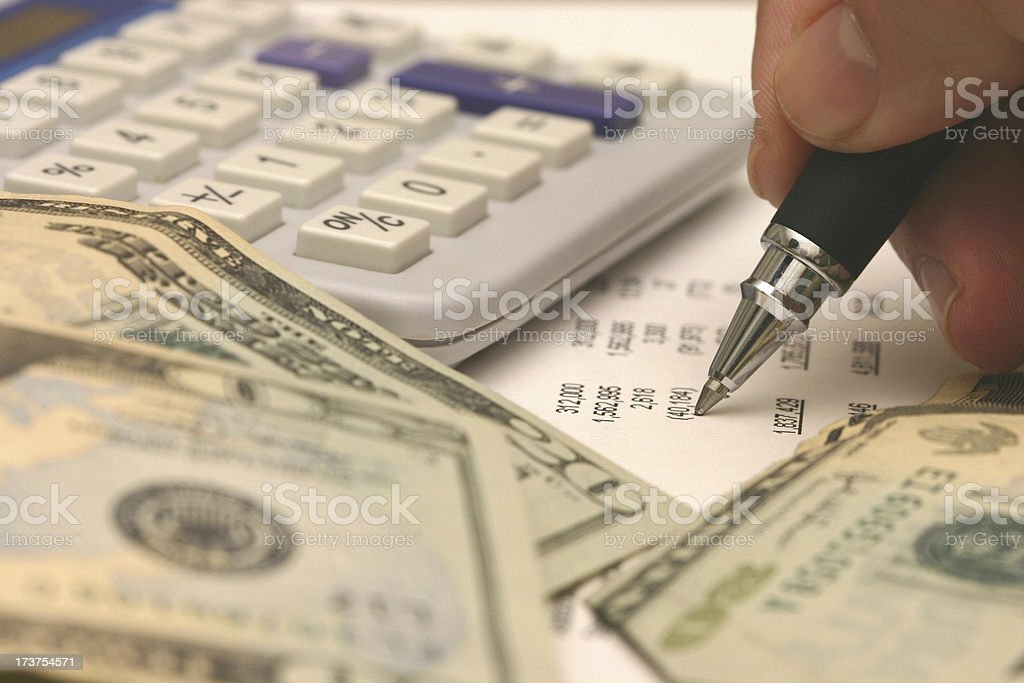 Close up of twenty dollar bills, calculator, and pen royalty-free stock photo