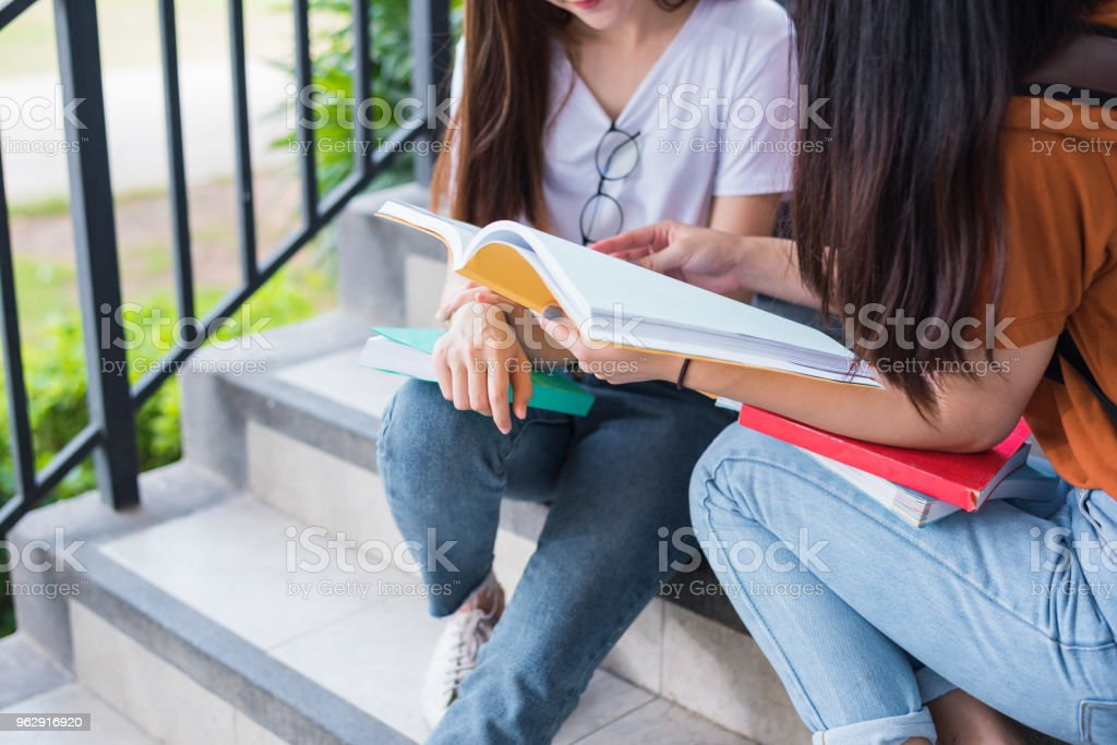 Close up of two Asian beauty girls reading and tutoring books for final  examination together. Student smiling and sitting on stair.