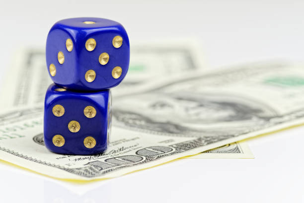 Close up of two blue dices lying on American dollars stock photo
