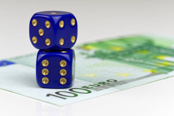 Close up of two blue dices lying on euro banknote stock photo