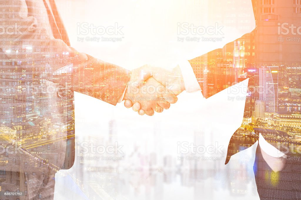 Close up of two businessmen's hands. Two cities, toned royalty-free stock photo