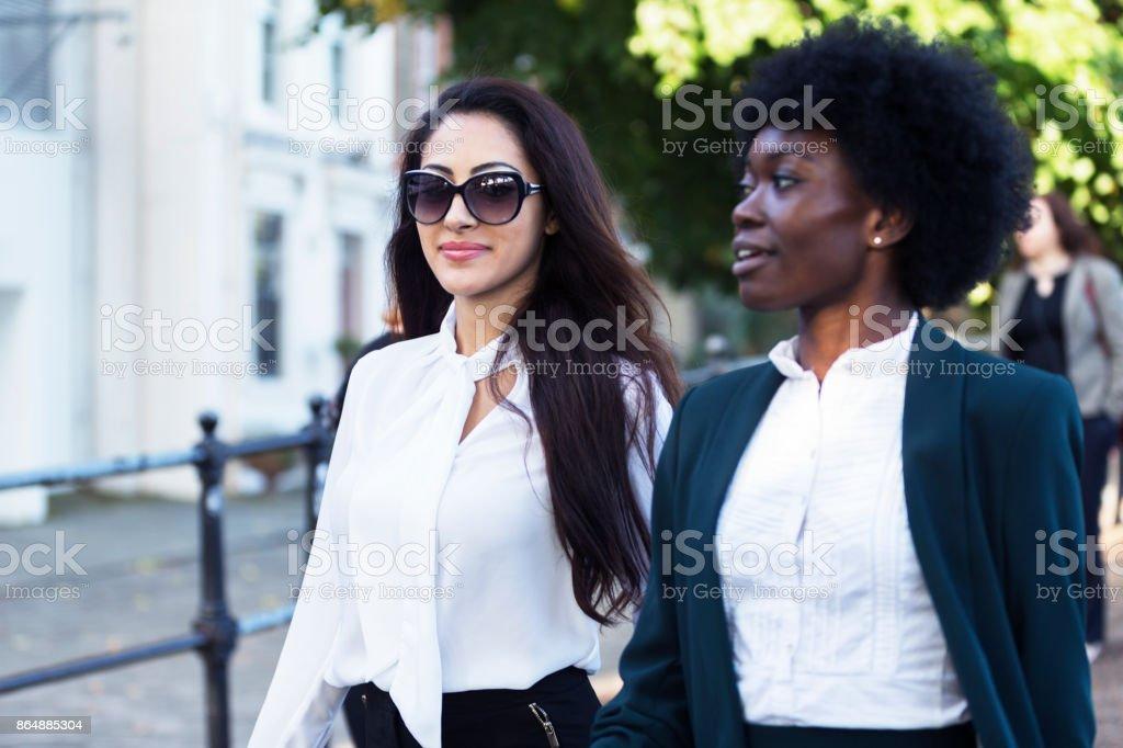 Cerca de dos mujeres empresarias en Londres afterwork; hablar y caminar - foto de stock