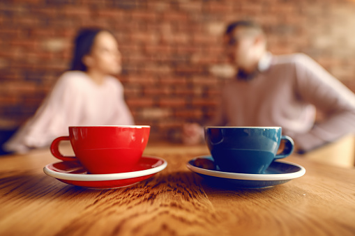 istock Close up of two cups of coffee on desk. In background blurred couple flirting. 1131995421