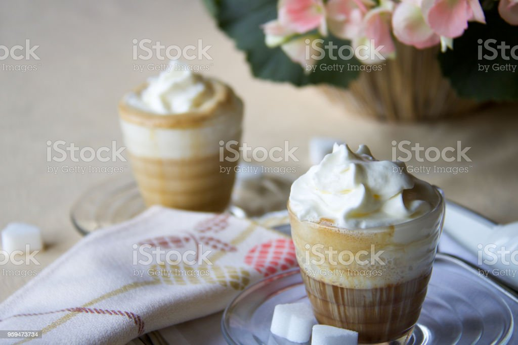close up of two cups of italian coffee with whipped cream on the table