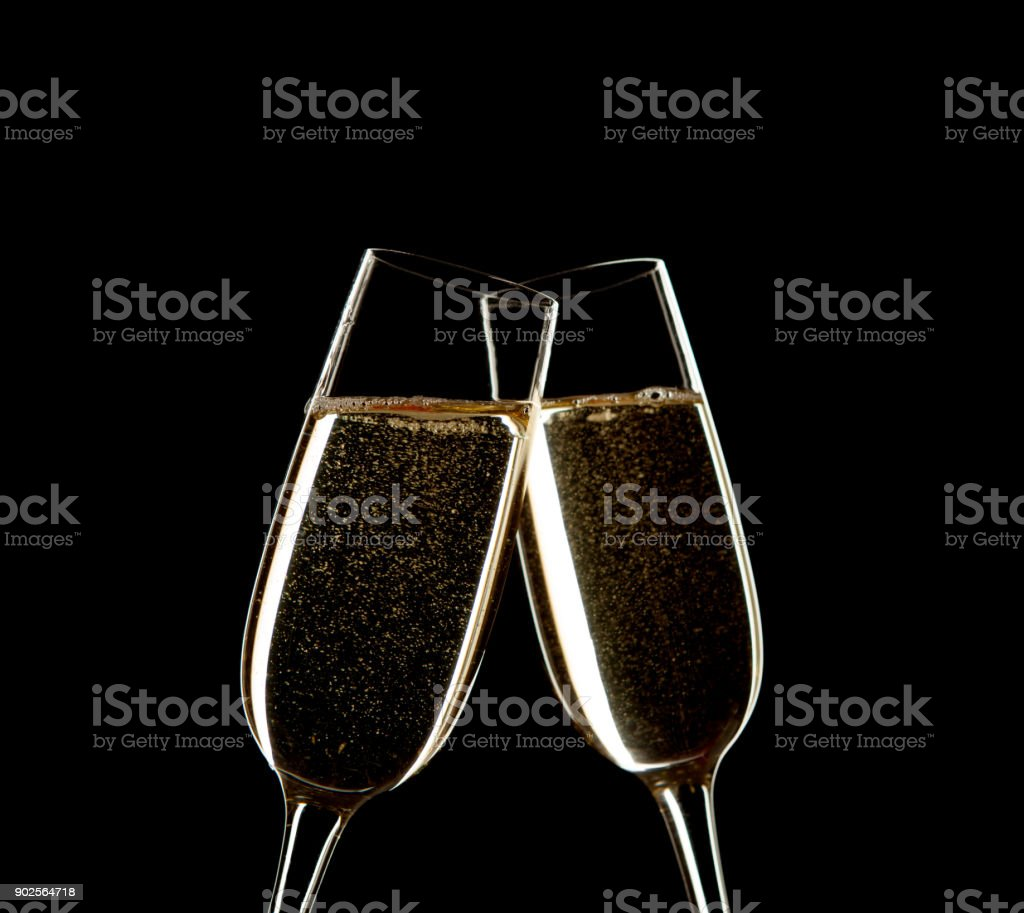 Close up of two glasses of Champagne clinking together isolated on black.   Celebration on New Year's Eve stock photo
