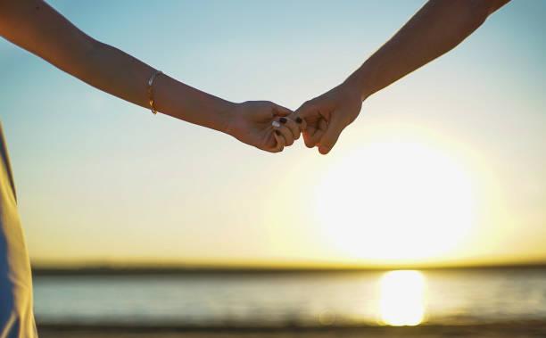 nahaufnahme von zwei liebenden verbinden hände. slow motion 240 fps. detail silhouette von mann und frau, die hand in hand über dem sonnenuntergang see hintergrund. paar vertrauen, liebe und glück konzept. - trust stock-fotos und bilder