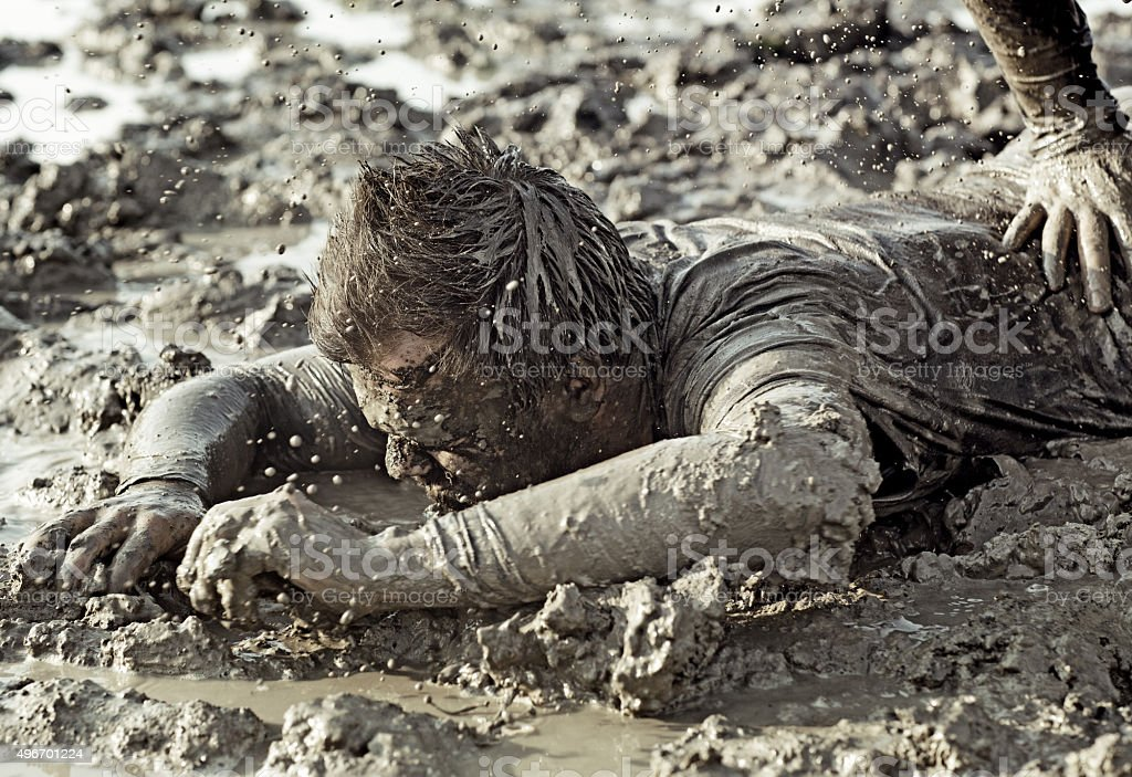close up of two man fighting in mud stock photo