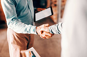 Close up of two modern businessman shaking hands for good negotiations and standing in warehouse.